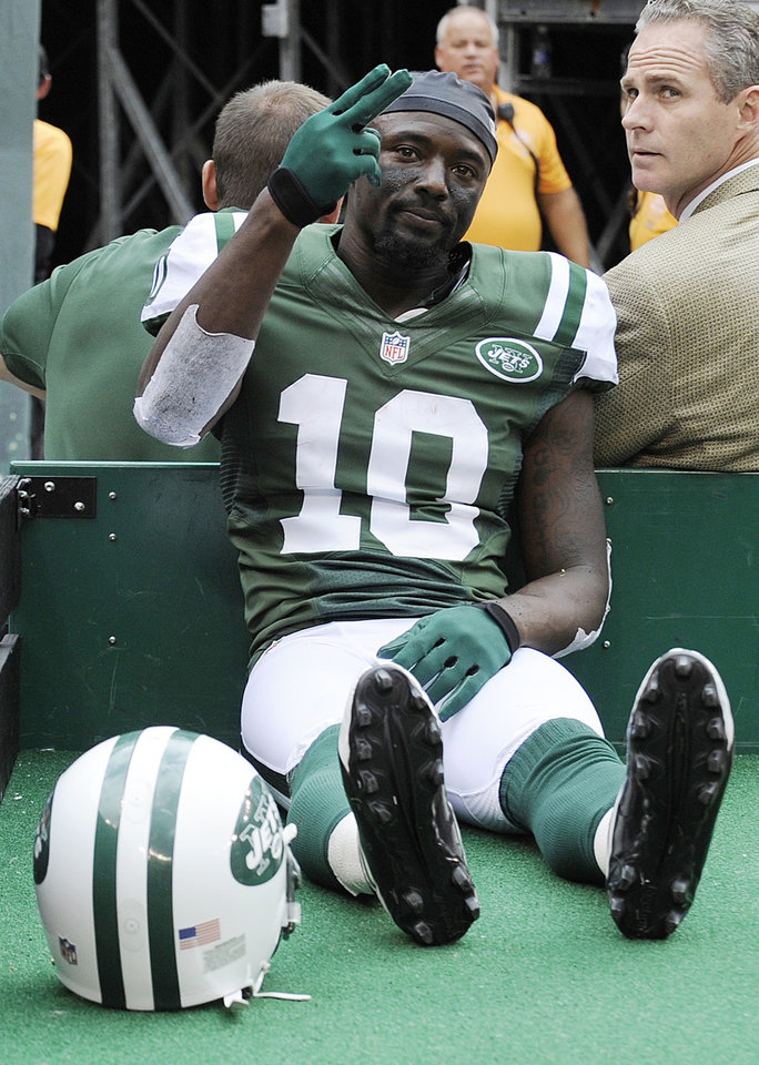 New York Jets wide receiver Santonio Holmes (10) gestures to fans as he is carted off the field after being injured during the second half of an NFL football game against the San Francisco 49ers Sunday, Sept. 30, 2012, in East Rutherford, N.J. (AP Photo/Bill Kostroun)