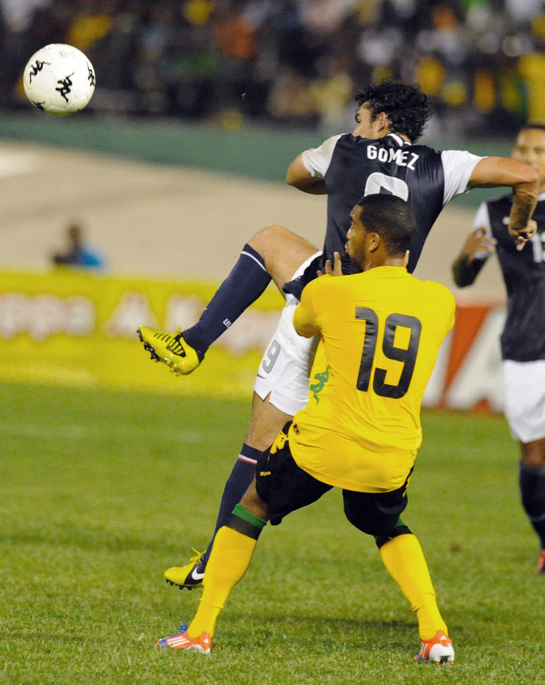 Photo -   United States' Herculez Gomez, rear, fights for the ball with Jamaica's Adrian Mariappa during a 2014 World Cup qualifying soccer match in Kingston, Jamaica, Friday, Sept. 7, 2012. (AP Photo/Collin Reid)