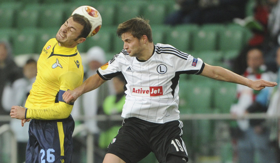 Photo - FILE -In this Thursday, Nov. 28, 2013 file photo Legia Warsaw's Bartosz Bereszynski   Lazio's Stefan Radu, left, challenge for the ball during their Europa League Group J soccer match between Legia Warszawa and Lazio Rome  in Warsaw, Poland. UEFA said Friday Auc. 8, 2014, Scottish side Celtic has been reinstated to the Champions League playoffs after qualifying-round opponent Legia Warsaw was punished for fielding Bartosz Bereszynski  an ineligible player. Legia won the third-round match 6-1 on aggregate after following up a 4-1 victory in the first leg with a 2-0 win at Murrayfield on Wednesday. But the Polish side brought on Bartosz Bereszynski as an 86th-minute substitute in the second leg, even though he was suspended for the game. (AP Photo/Alik Keplicz, File)