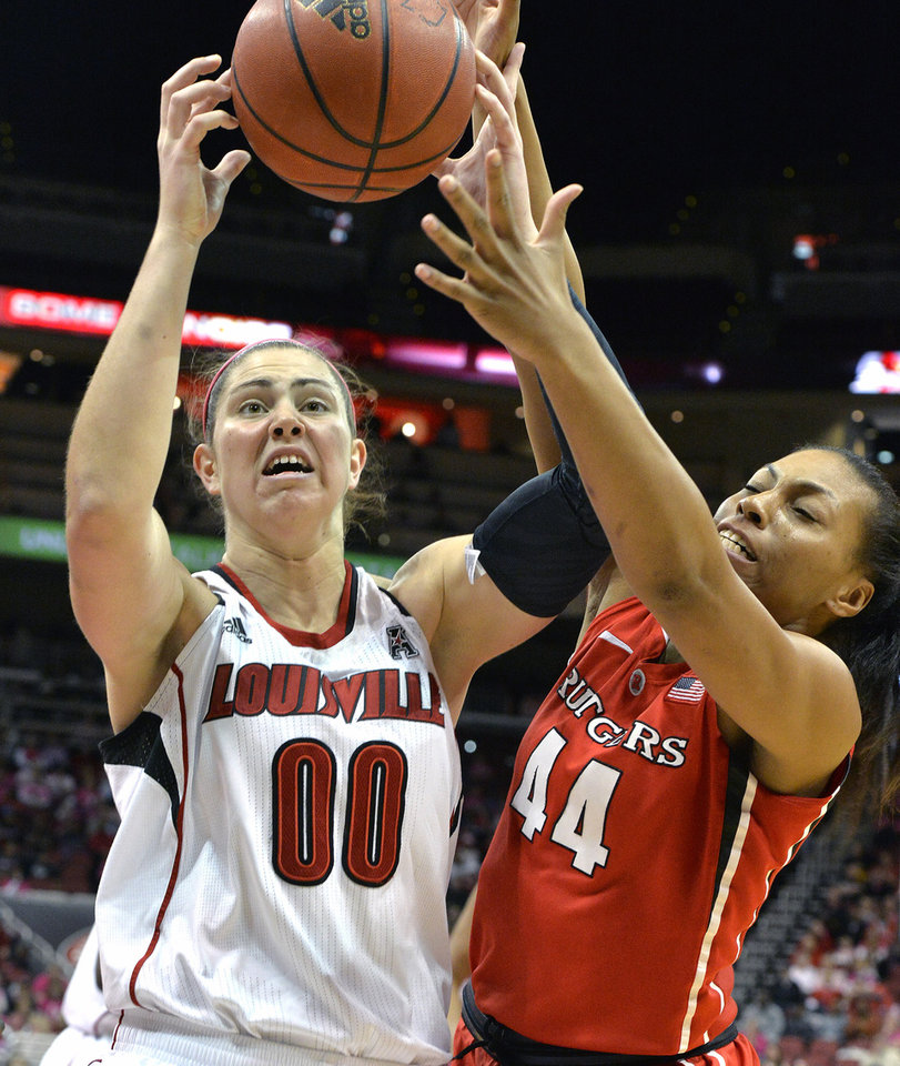 Photo - Louisville's Sara Hammond, left, battles Rutgers'  Betnijah Laney for a rebound during the first half of an NCAA college basketball game, Sunday, Feb. 23, 2014, in Louisville, Ky. (AP Photo/Timothy D. Easley)