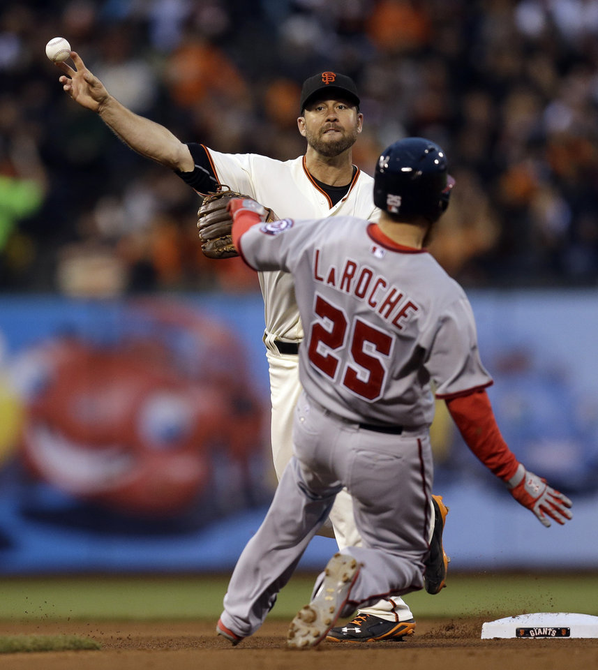 Photo - San Francisco Giants second baseman Brandon Hicks throws over Washington Nationals' Adam LaRoche to complete a double play in the fourth inning of a baseball game Tuesday, June 10, 2014, in San Francisco. Washington's Ryan Zimmerman was out at first base. (AP Photo/Ben Margot)
