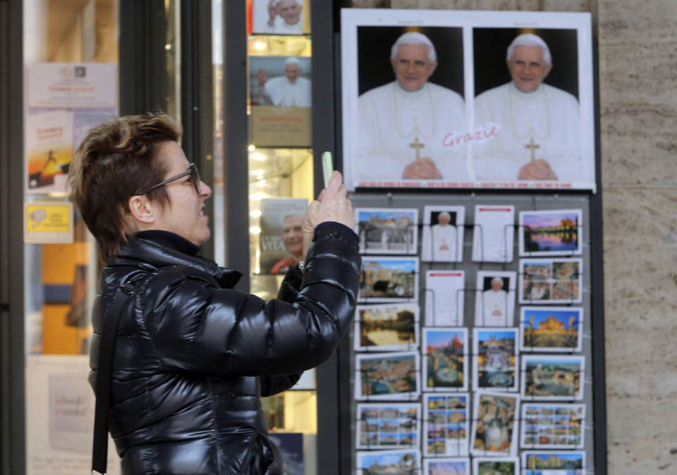 "A woman takes photos next to portraits of Pope Benedict XVI, outside a bookshop near the Vatican, Tuesday, Feb. 26, 2013. Pope Benedict XVI will be known as ""emeritus pope"" in his retirement and will continue to wear a white cassock, the Vatican announced Tuesday, again fueling concerns about potential conflicts arising from having both a reigning and a retired pope. The pope's title and what he would wear have been a major source of speculation ever since Benedict stunned the world and announced he would resign on Thursday, the first pontiff to do so in 600 years. (AP Photo/Dmitry Lovetsky)"