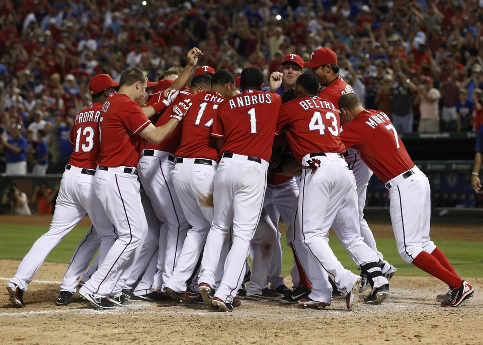 Photo - Texas Rangers' teammates swarm Geovany Soto after his walk-off home run against the Los Angeles Angels during the ninth inning of a baseball game, Monday, July 29, 2013, in Arlington, Texas. The Rangers won 4-3. (AP Photo/Jim Cowsert)