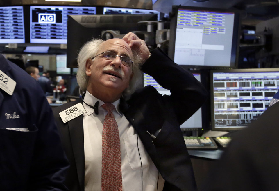Photo -  Trader Peter Tuchman works Monday on the floor of the New York Stock Exchange. Global stock markets are down sharply on tensions over Russia's military advance into Ukraine and the threat of sanctions by Western governments. AP photo   Richard Drew -