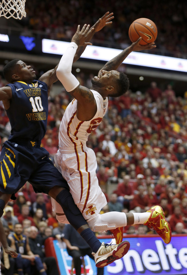 Photo - West Virginia guard Eron Harris tries to stop the shot of Iowa State guard DeAndre Kane during the first half of an NCAA college basketball game in Ames, Iowa, Wednesday, Feb. 26, 2014. (AP Photo/Justin Hayworth)