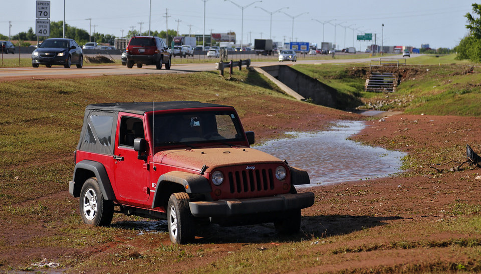 Photo - A car sits in a ditch after being washed off the road due to flood waters in Moore, Okla. on Thursday, May 7, 2015. The area was flooded by Wednesday's storms. Photo by Chris Landsberger, The Oklahoman