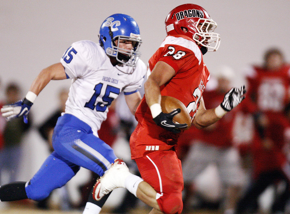 Photo - Purcell's Damian Shea (28) carries the ball past Brandon Carlton (15) of Bridge Creek during a high school football playoff game between Purcell and Bridge Creek at Conger Field in Purcell, Okla.,Friday, Nov. 11, 2011. Photo by Nate Billings, The Oklahoman