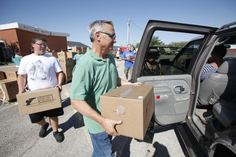 Photo - Volunteers Blake Roberts, left, 16yr. and Steve Eaton load a car during a joint food drive with Feed The Children and Mustard Seed Development Corporation   in Oklahoma City, Tuesday 25, 2012. Photo By Steve Gooch, The Oklahoman