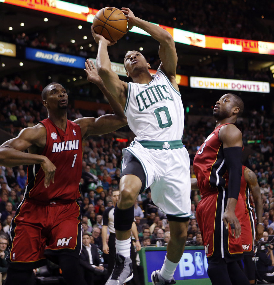 Photo - Boston Celtics' Avery Bradley (0) shoots between Miami Heat's Chris Bosh (1) and Dwyane Wade (3) in the first quarter of an NBA basketball game in Boston, Monday, March 18, 2013. (AP Photo/Michael Dwyer)