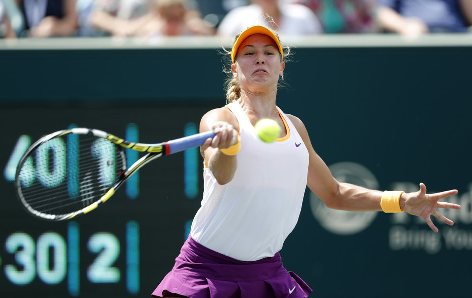 Photo - Eugenie Bouchard, of Canada, returns to Jelena Jankovic, of Serbia, during the Family Circle Cup tennis tournament in Charleston, S.C., Friday, April 4, 2014. (AP Photo/Mic Smith)