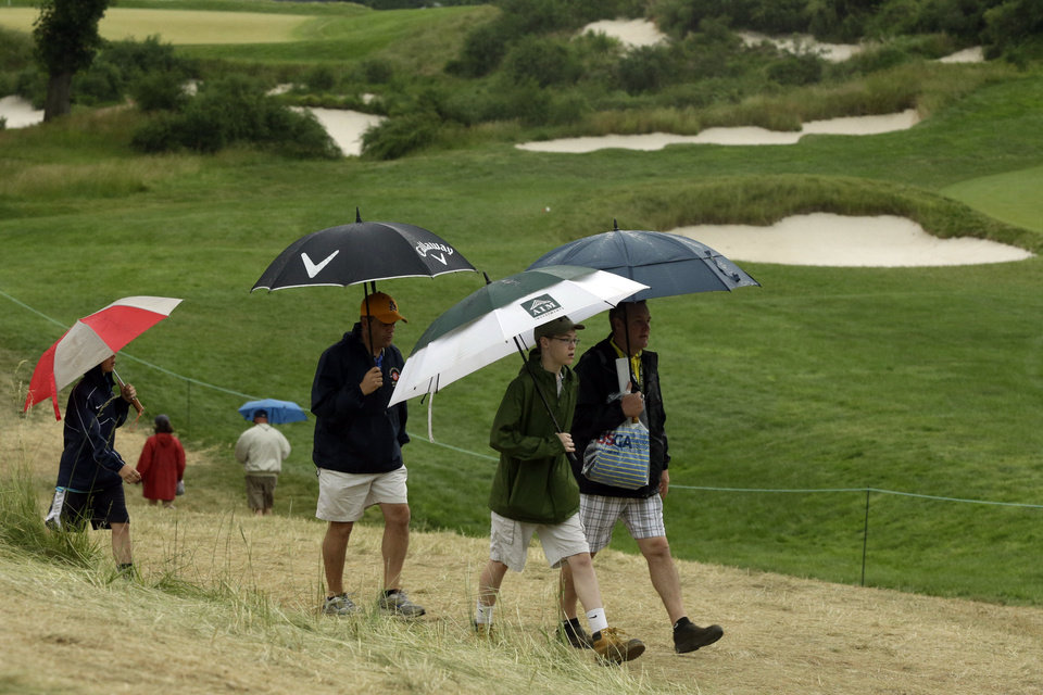 Photo - Spectators walk off the course as weather delays the first round of the U.S. Open golf tournament at Merion Golf Club, Thursday, June 13, 2013, in Ardmore, Pa. (AP Photo/Gene J. Puskar)