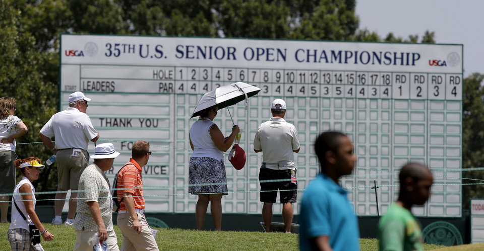 Photo - Fans walk past a leader board during a practice round for the U.S. Senior Open at Oak Tree National in Edmond, Okla., Tuesday, July 8, 2014. Photo by Bryan Terry, The Oklahoman