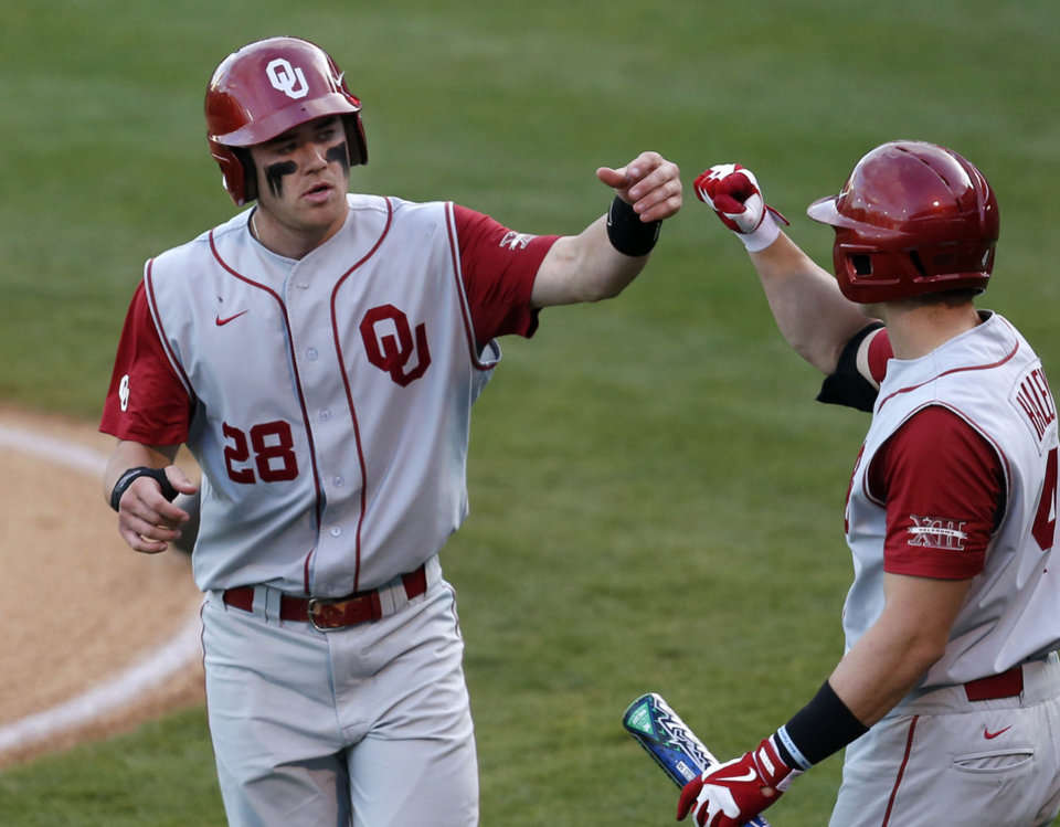 Photo - Oklahoma's Mac James, left, is greeted at the dugout after scoring against Oklahoma State during an NCAA college baseball game in Tulsa, Okla., on Saturday, May 17, 2014. (AP Photo/Tulsa World, Matt Barnard)