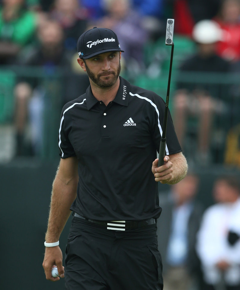 Photo - Dustin Johnson of the US acknowledges the crowd after holing his putt on the 1st green during the third day of the British Open Golf championship at the Royal Liverpool golf club, Hoylake, England, Saturday July 19, 2014. (AP Photo/Jon Super)