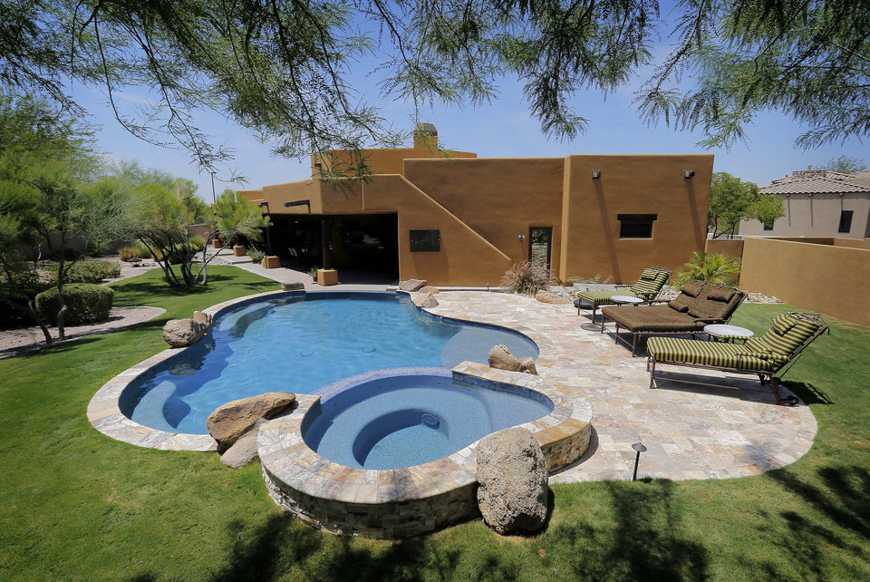 Photo - This is an exterior view of a luxury custom home with a listing price of $1 million on Wednesday, July 30, 2014 in Mesa, Ariz. The more than 4,000-square-foot home has a resort style back yard, pool and hot tub, four bedrooms, three full and one partial bathrooms, a gourmet kitchen and travertine tile throughout the home. (AP Photo/Matt York)
