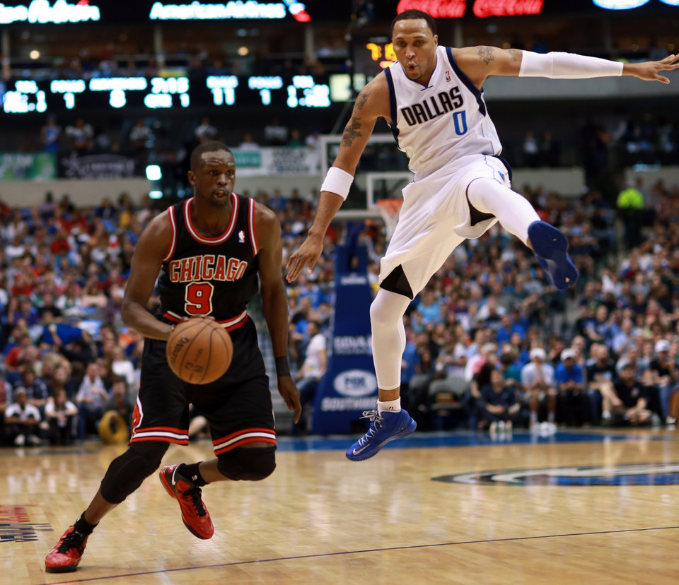 Chicago Bulls forward Luol Deng (9) makes an offensive move as Dallas Mavericks forward Shawn Marion (0) leaps through the air in an attempt to defend during the first half of an NBA basketball game, Saturday, March 30, 2013, in Dallas. (AP Photo/ Michael Mulvey)
