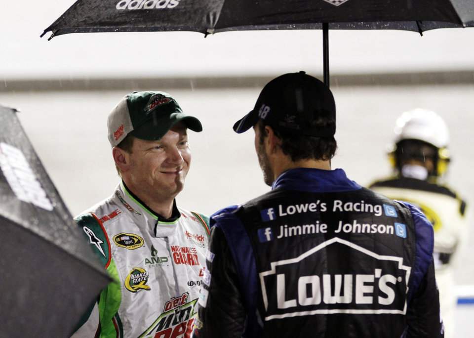 Photo -   Dale Earnhardt Jr., left, talks with Jimmie Johnson, right, during a rain delay for the NASCAR Sprint Cup Series auto race at Richmond International Raceway in Richmond, Va., Saturday, Sept. 8, 2012. (AP Photo/Steve Helber)