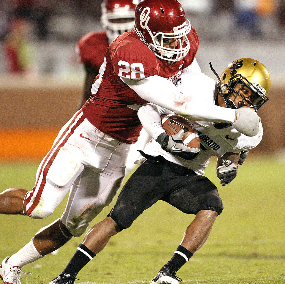 OU's Travis Lewis, left, tackles Rodney Stewart during the second half of a 2010 game against Colorado. Lewis, who plays almost every defensive snap at weak-side linebacker, could see time at middle linebacker or get a few more snaps to rest with the emergence of Corey Nelson. Photo by Steve Sisney, The Oklahoman