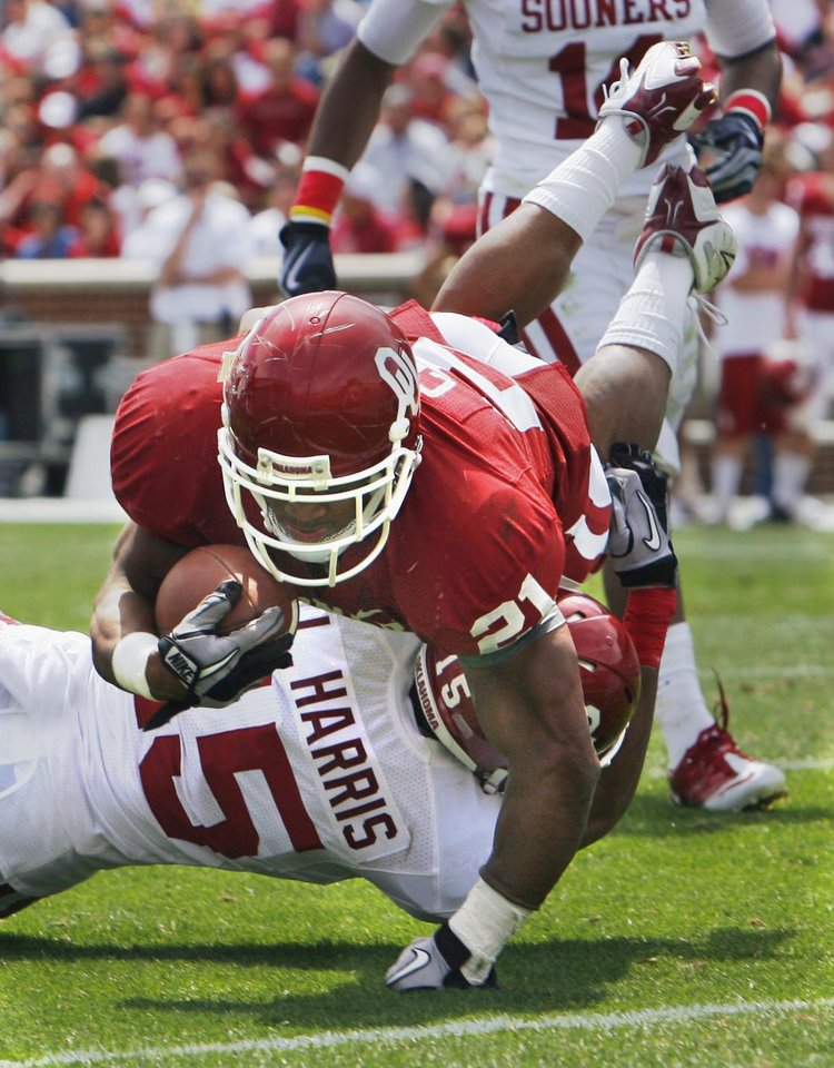Photo - Running back Clay Brennan (21) scores over the goal line tackle of Lamar Harris (15) during the University of Oklahoma Sooner's (OU) Spring Football game at Gaylord Family-Oklahoma Memorial Stadium on Saturday, April 16, 2011, in Norman, Okla.  