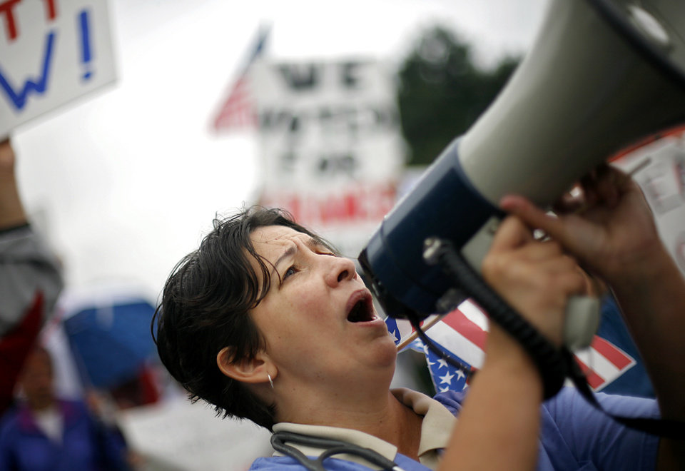 Photo - Reggie Cervantes, of Yukon leads a chant during a Health Care Reform march to the south side of the State Capitol in Oklahoma City on Sunday, Sept. 13, 2009.  By John Clanton, The Oklahoman
