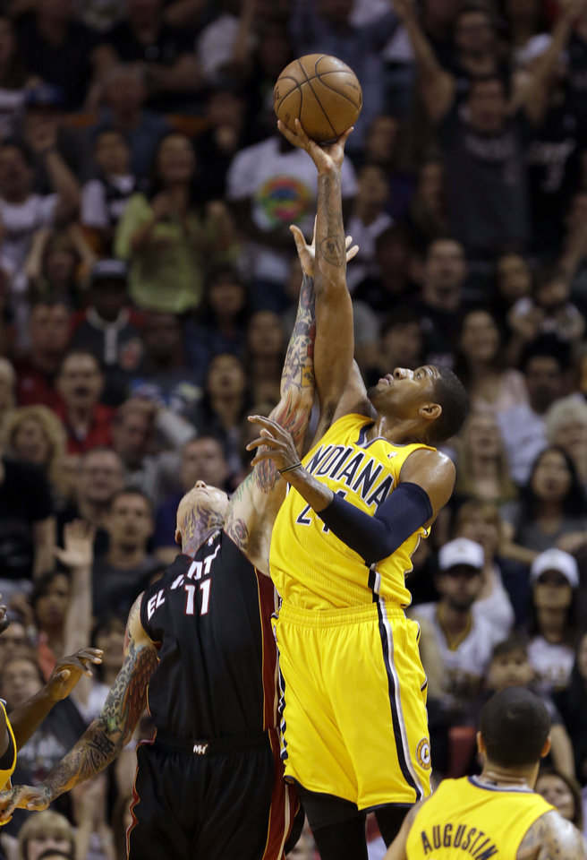 Photo - Indiana Pacers' Paul George (24) recovers a rebound over Miami Heat's Chris Andersen (11) during the first half of an NBA basketball game in Miami, Sunday, March 10, 2013. (AP Photo/Alan Diaz)