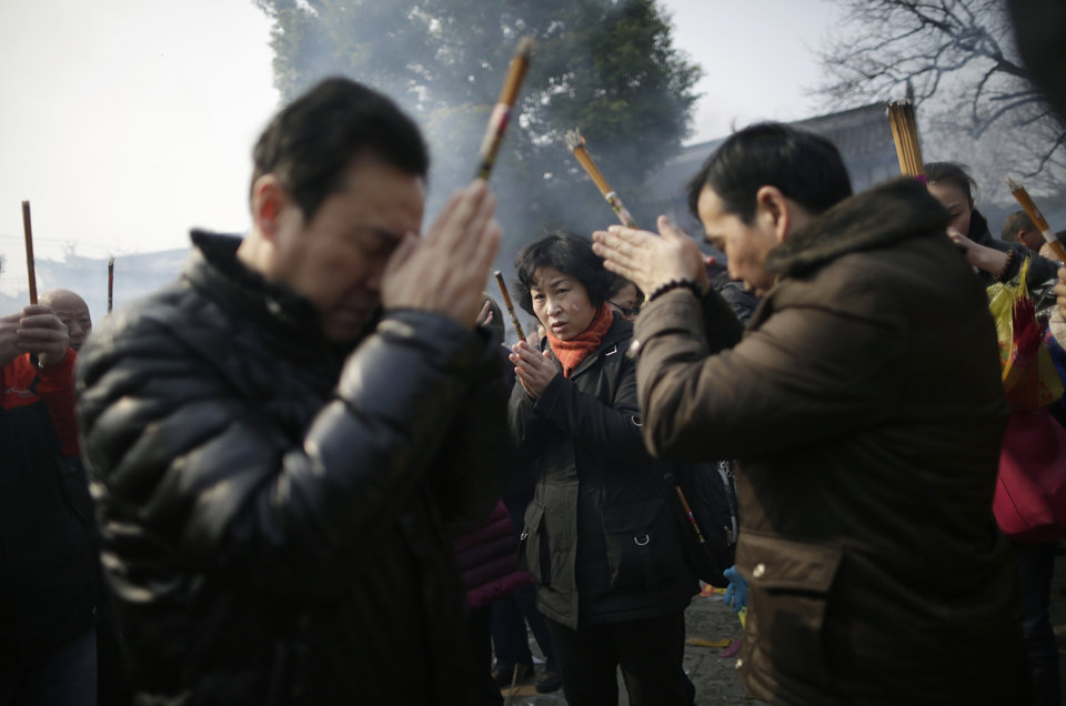 People burn joss sticks while praying at Longhua Temple on the first day of the Lunar New Year in Shanghai, China on Sunday, Feb. 10, 2013.  Millions across China are celebrating the arrival of the Lunar New Year, the Year of the Snake, marked with a week-long Spring Festival holiday.   (AP Photo/Eugene Hoshiko)