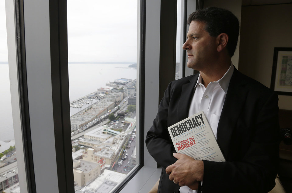 Photo - FILE - In this Aug. 2, 2013 file photo, venture capitalist Nick Hanauer stands by the window of his office in downtown Seattle. He holds a copy of
