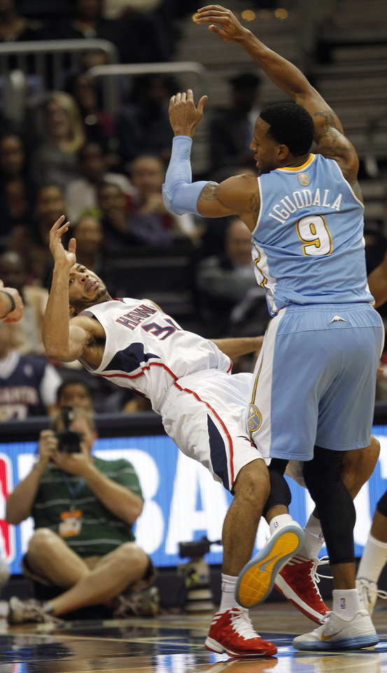 Atlanta Hawks point guard Devin Harris (34) is fouled by Denver Nuggets shooting guard Andre Iguodala (9) during the first half of an NBA  basketball game on Wednesday, Dec. 5, 2012, in Atlanta. (AP Photo/John Bazemore)