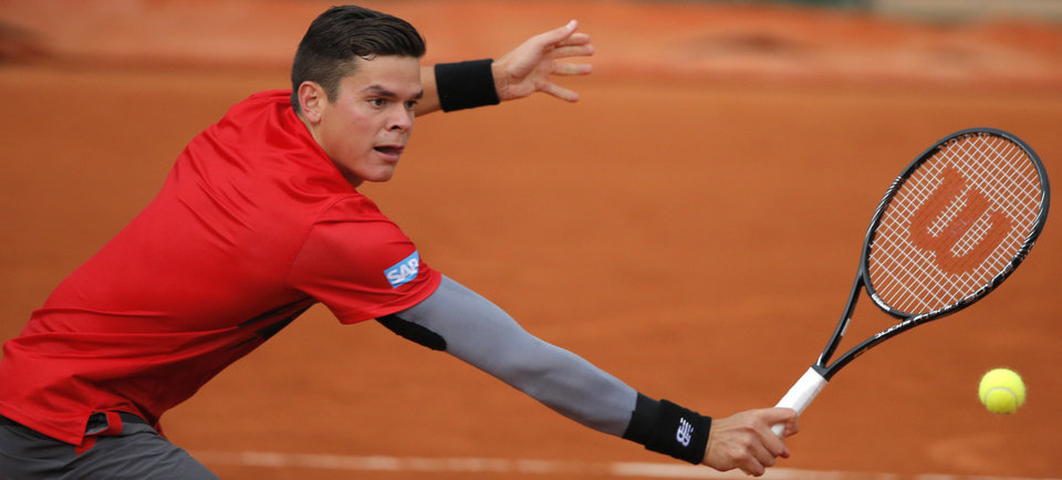 Photo - Canada's Milos Raonic returns in the fourth round match of the French Open tennis tournament against Spain's Marcel Granollers at the Roland Garros stadium, in Paris, France, Sunday, June 1, 2014. Raonic won in three sets 6-3, 6-3, 6-3. (AP Photo/Michel Spingler)