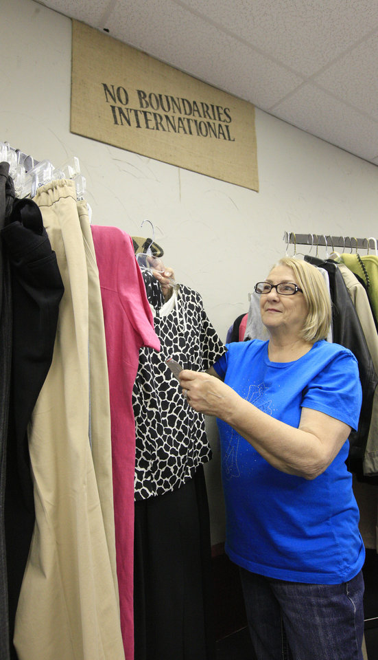 Photo -  Volunteer Mary Meador of Oklahoma City, places donated clothing on a rack at Carina's Closet, a free clothing distribution site operated by No Boundaries International.   PAUL B. SOUTHERLAND -  PAUL B. SOUTHERLAND