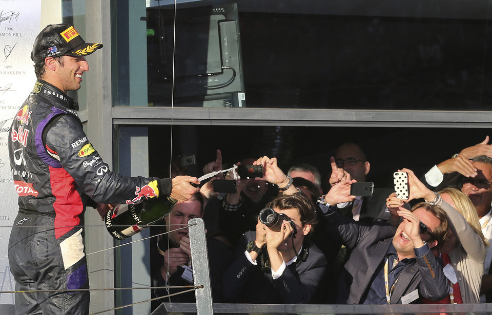 Photo - Red Bull driver Daniel Ricciardo of Australia sprays champagne in celebration after finishing second in the Australian Formula One Grand Prix at Albert Park in Melbourne, Australia, Sunday, March 16, 2014. Mercedes driver Nico Rosberg of Germany won the race. (AP Photo/Rob Griffith)