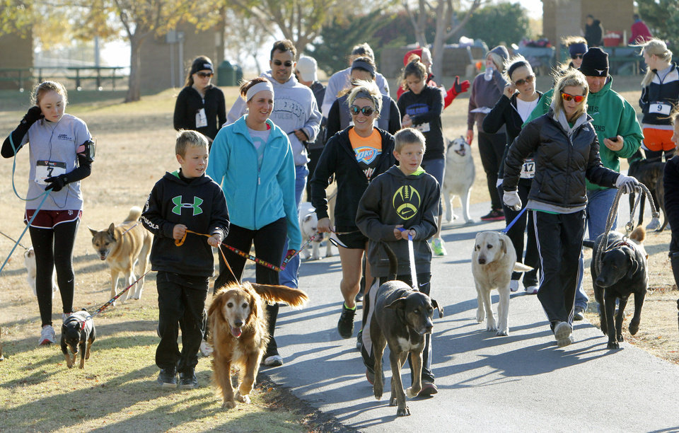 Dogs and their owners participate in the Doggie Dash 5k run at J.L. Mitch Park in Edmond. The event is a fundraiser created by a woman who is going to India to teach orphans. PHOTO BY PAUL HELLSTERN, THE OKLAHOMAN