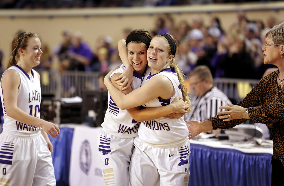 Photo - Morgan Vogt and Madi Grellner, right, embrace as they come off the court in the closing minute of the  Class B girls high school basketball championship game in the Jim Norick Arena at State Fair Park on  Saturday, March 8, 2014. At left is Laci Friesen. Okarche defeated Red Oak, 66-41. Photo by Jim Beckel, The Oklahoman