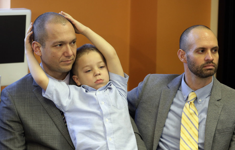 Photo - Plaintiffs Matthew Barraza, left, and his husband Tony Milner, right, look on as their son Jesse, 4, plays, during a news conference on Tuesday, Jan. 21, 2014, in Salt Lake City. The American Civil Liberties Union has sued the state of Utah over the issue of gay marriage, saying the official decision to stop granting benefits for newly married same-sex couples has created wrenching uncertainty. The lawsuit filed Tuesday says the state has put hundreds of gay and lesbian couples in legal limbo and prevented them from getting key protections for themselves and their children. (AP Photo/Rick Bowmer)