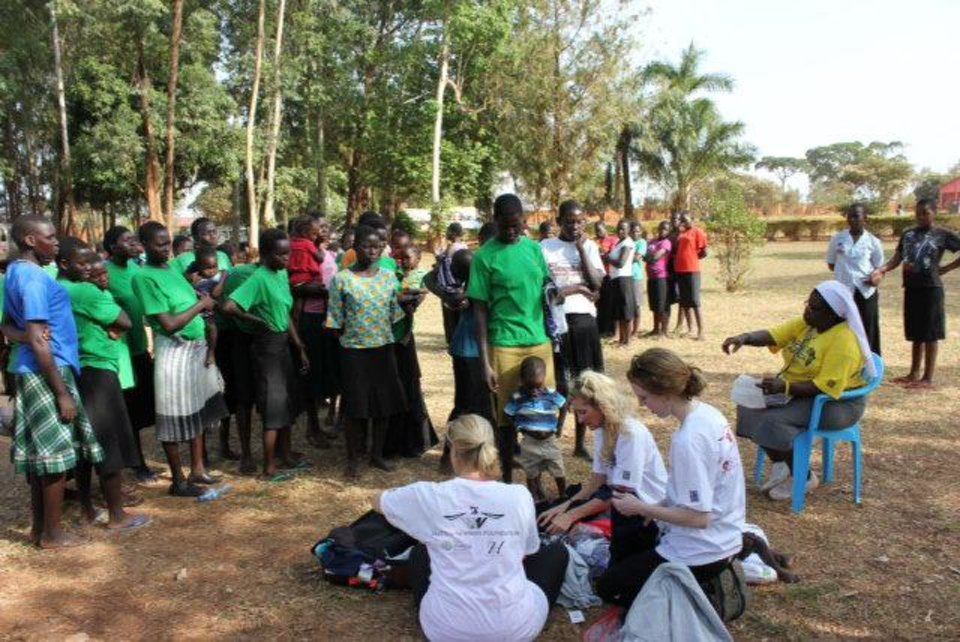 Young women from the St. Monica's Girls School in Uganda, Africa, watch as volunteers from Oklahoma show them how to crochet pop-tab purses. Photo provided <strong></strong>