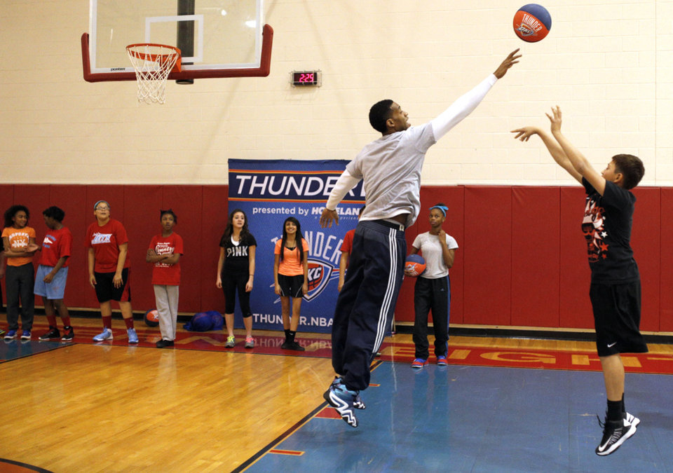 Photo - Oklahoma City Perry Jones III l blocks the shot of Bryan Salinas during a Thunder Fit clinic at Western Heights Middle School in Oklahoma City, Friday, Jan. 10, 2014. The event coincided with NBA Fit Week.  PHOTO BY SARAH PHIPPS, The Oklahoman