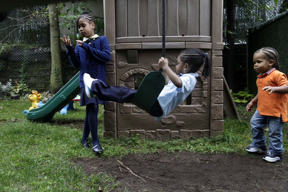 Photo -   Malayasia Blackwood, 7, left, her brother Omarhie Blackwood, 1, right, and Rihanna Hall, 3, play in the yard of the Drew House in New York, Wednesday, Oct. 3, 2012. The program, called Drew House, is one of a kind in the nation, where mothers arrested on felonies can live with their children, instead of in prison. The program has been lauded as a success that should be replicated around the country, but the small house is already full, and without additional funding and space, it can't grow. (AP Photo/Seth Wenig)