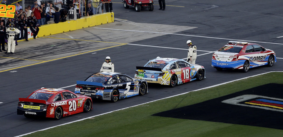 Officials gather around Kyle Busch (18), Kasey Kahne (5) and Matt Kenseth (20) during a red flag caused by a broken television camera cable rig potentially damaging cars during the NASCAR Sprint Cup Series Coca-Cola 600 auto race at Charlotte Motor Speedway in Concord, N.C., Sunday, May 26, 2013. (AP Photo/Gerry Broome)