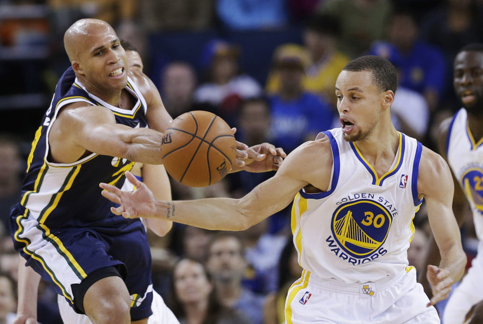 Photo - Golden State Warriors guard Stephen Curry (30) strips the ball from Utah Jazz forward Richard Jefferson, left, during the first half of an NBA basketball game Sunday, April 6, 2014, in Oakland, Calif. (AP Photo/Marcio Jose Sanchez)