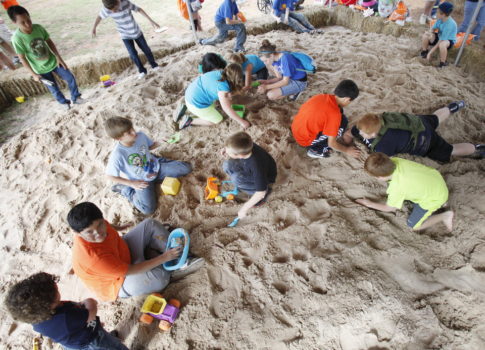 Photo - Children play in a large sand pile during school day of the Oklahoma Wildlife Expo at the Lazy E Arena and Ranch in Guthrie, OK, Friday, September 28, 2012,  By Paul Hellstern, The Oklahoman