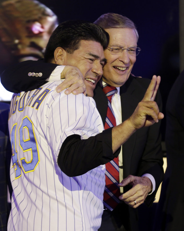 Photo - Baseball commissioner Bud Selig hugs Teddy Higuera during a Milwaukee Brewers Wall of Honor ceremony before a baseball game between the Milwaukee Brewers and the Cincinnati Reds Friday, June 13, 2014, in Milwaukee. (AP Photo/Morry Gash)