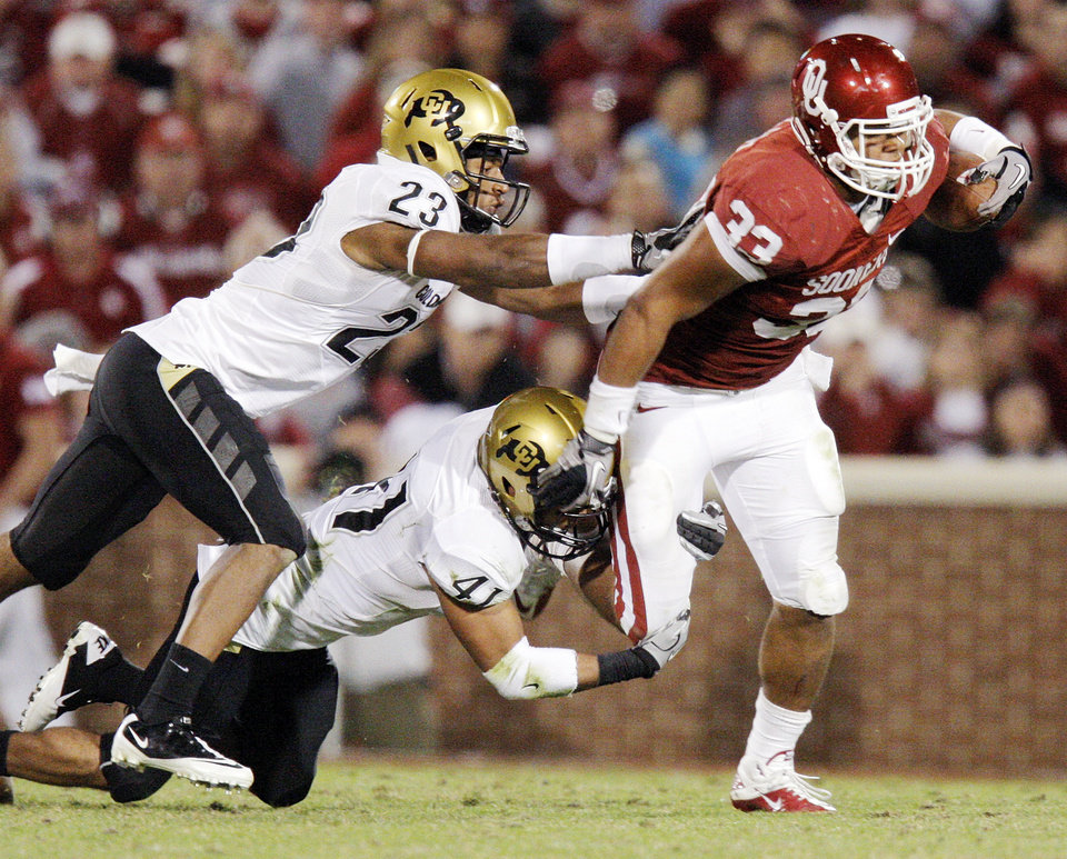 Photo - Colorado's Jalil Brown (23) and Terrel Smith (41) try to bring down OU's Trey Millard (33) on the third quarter during the college football game between the University of Oklahoma (OU) Sooners and the University of Colorado Buffaloes at Gaylord Family-Oklahoma Memorial Stadium in Norman, Okla., Saturday, October 30, 2010. Photo by Nate Billings, The Oklahoman