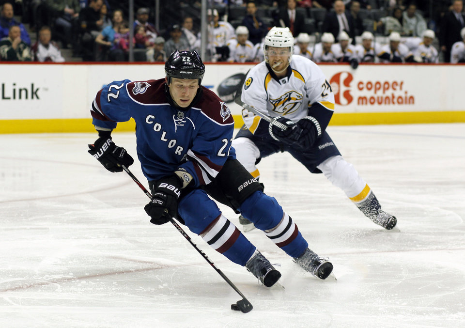 Photo - Colorado Avalanche defenseman Matt Hunwick, front, picks up a loose puck as Nashville Predators right eing Mastt Halischuk covers in the second period of an NHL hockey game in Denver on Saturday, March 30, 2013. (AP Photo/David Zalubowski)
