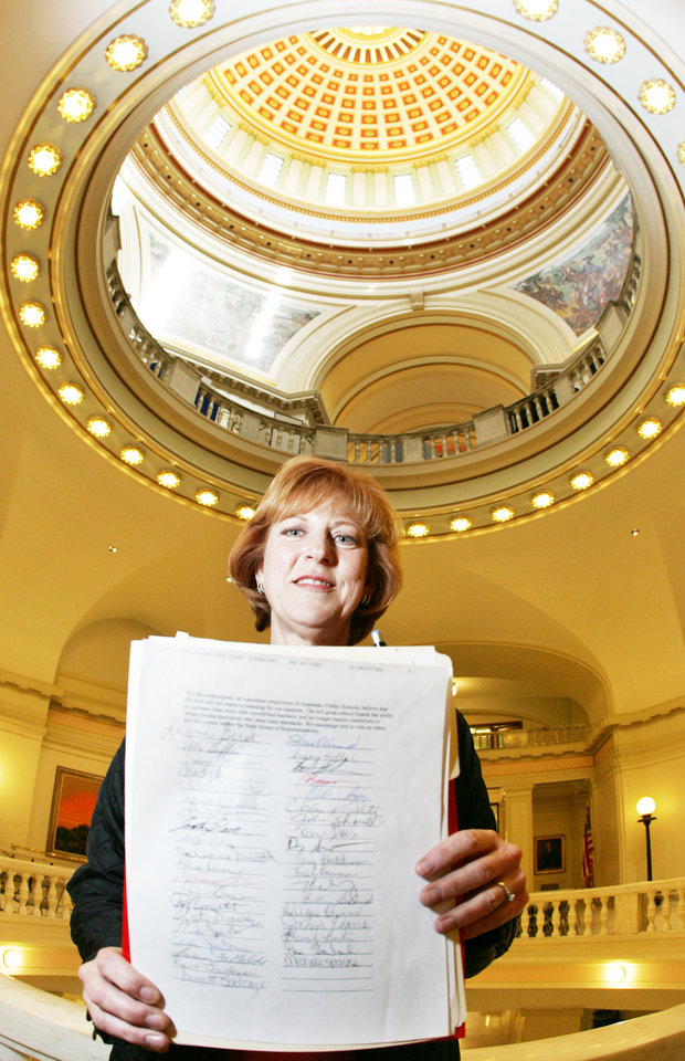 Photo - Anadarko music teacher Pamela Martin holds a list with signatures from Oklahoma educators concerned about Senate Bill 834 at the state Capitol on Wednesday in Oklahoma City.  BY STEVE GOOCH, THE OKLAHOMAN.