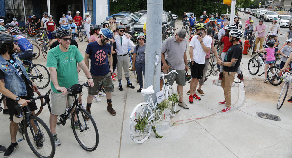 Photo - Bicyclists gather at the Ghost Bike Memorial for Chad Epley. Dozens of bicyclists ride along Classen Boulevard Tuesday, May 7, 2019, to highlight the need for better bike lanes, stopping at 16th and Classen Blvd. where a ghost bike memorial for Chad Epley who was killed at the intersection while riding home after work.  Photo by Doug Hoke.