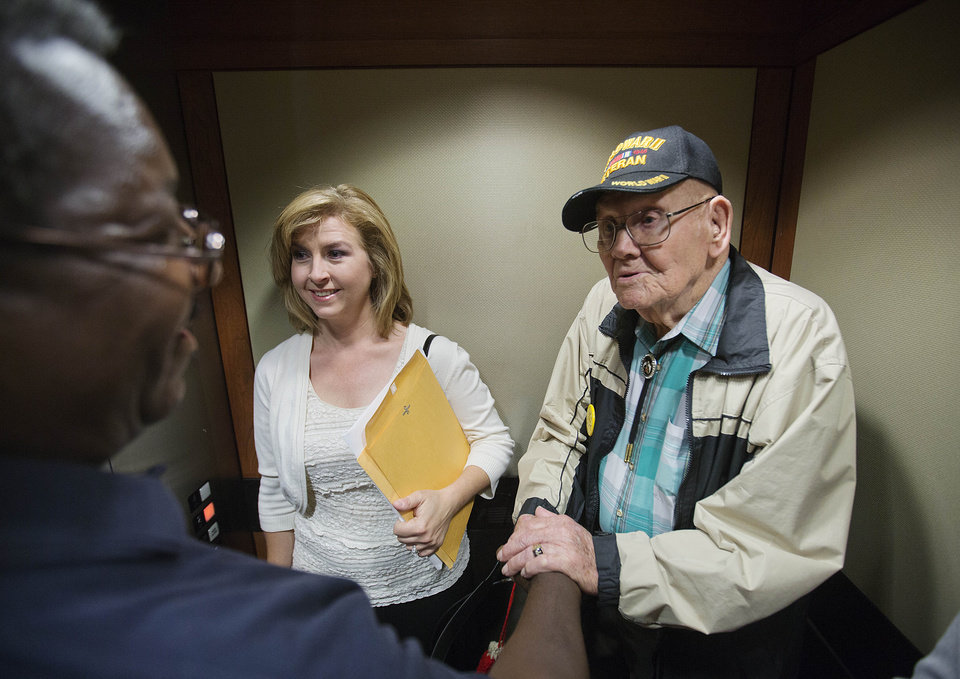 Photo - Ninety-four-year-old World War II veteran Sherwin Callander, right, is greeted by retired Staff Sgt. and current U.S. Citizenship and Immigration Services officer Roger Williams, left, while riding in an elevator with his granddaughter Elaine Oakes, following a naturalization ceremony, Monday, June 2, 2014, in Atlanta. The World War II veteran from Alabama is headed to France for D-Day ceremonies, a trip that seemed unlikely just last week. Callander read about ceremonies for the 70th anniversary of D-Day and thought it would be meaningful to go. He hadn't been back to France since landing on Utah Beach during the Battle of Normandy, but he hit a snag when he went to get a passport. Callander was born in Canada to an American mother, and his family moved to the U.S. when he was 3. But he didn't have documentation proving his U.S. citizenship. Federal officials heard his story and on Monday gave him a proof of citizenship certificate so he could get a passport in time to leave for France just hours later. (AP Photo/David Goldman)