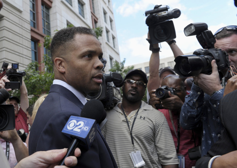 Photo - Former Illinois Rep. Jesse Jackson Jr., leaves federal court in Washington, Wednesday, Aug. 14, 2013. Jackson was sentenced to two and a half years in prison Wednesday after pleading guilty to scheming to spend $750,000 in campaign funds on TV's, restaurant dinners, an expensive watch and other costly personal items. His wife received a sentence of one year.  (AP Photo/Susan Walsh)