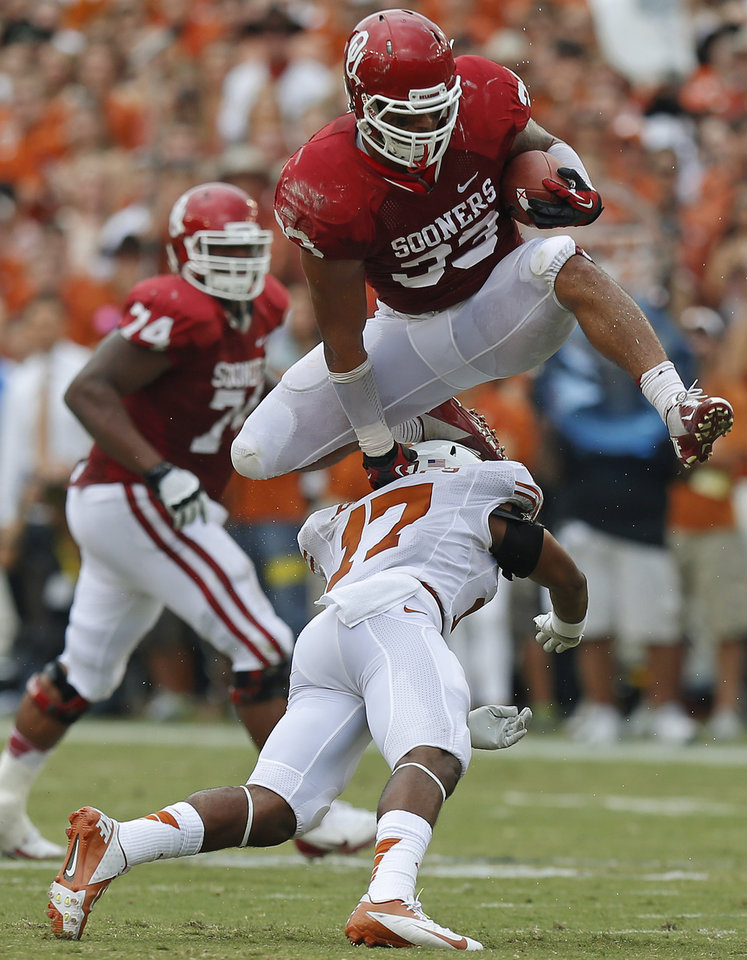 OU\'s Trey Millard (33) leaps over UT\'s Adrian Phillips (17) during the Red River Rivalry college football game between the University of Oklahoma (OU) and the University of Texas (UT) at the Cotton Bowl in Dallas, Saturday, Oct. 13, 2012. Photo by Bryan Terry, The Oklahoman