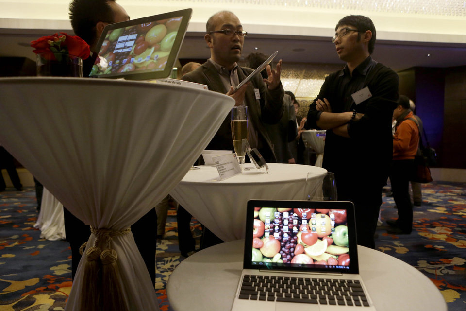 In this photo taken on Dec. 4, 2012, a Huawei staff member, right, talks to journalists near laptops and tablets manufactured by Huawei during a media event at a hotel in Beijing Tuesday. Chinese tech giant Huawei on Monday, Jan. 21, 2013 criticized U.S. claims the company might be a security risk as trade protectionism that harms consumers. The comments came as Huawei Technologies Ltd., a maker of network switching gear and smartphones, disclosed details of its 2012 performance in an effort to show transparency and allay security concerns. (AP Photo/Ng Han Guan)