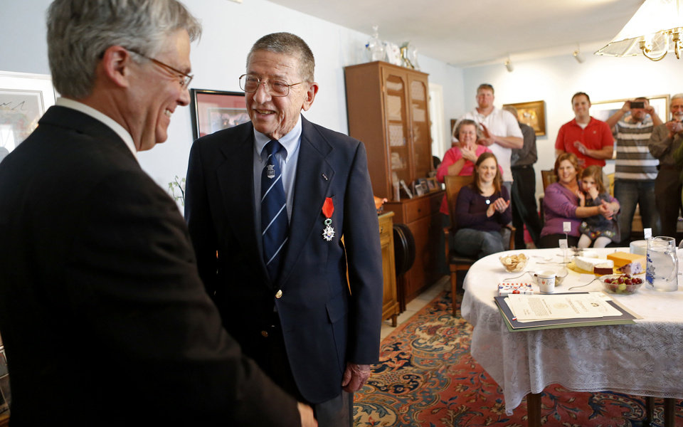 Photo - Retired Maj. Gen. Stanley Newman smiles after receiving the Medal of Chevalier of the French National Order of the Legion of Honor from Grant Moak, Honorary French Consul for Oklahoma, as friends and family watch inside his daughter's Oklahoma City home, Saturday, March 16, 2013. Photo by Bryan Terry, The Oklahoman